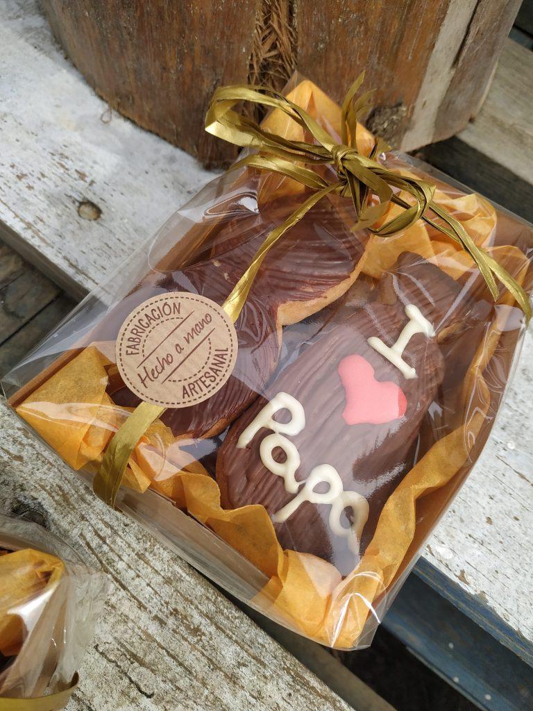 caja regalo para el día del padre compuesto de dos galletas de mantequilla: una corbata y un bigote, bañadas en chocolate. y debajo unas galletas de almendra y chocolate: kukiplanitas.